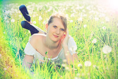 Beautiful redhead in nature. Beautiful redhead in white shirt lying in a grass, on a meadow, fashion photography Royalty Free Stock Image