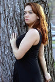 Beautiful redhead near a tree, sexy Royalty Free Stock Photography