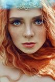 Beautiful redhead Norwegian girl with big eyes and freckles on face in the forest. Portrait of redhead woman closeup in nature royalty free stock images