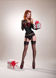 Beautiful redhead pin-up style girl holding gift box Royalty Free Stock Photos