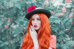 Beautiful redhead princess portrait. Ring with a blue stone on finger. Young unusual woman with long hair, red lips, pale skin on. Bkue spring background. Fine stock photography