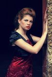 Beautiful redhead in red gown. And vest posing next to the doorjamb, fashion photography, cross processing Royalty Free Stock Image