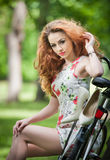 Beautiful redhead relaxing with bicycle in the summer park Royalty Free Stock Photos