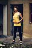 Beautiful redhead in shirt and leggings an old building. Beautiful redhead in yellow shirt and leggings posing an old building, fashion photography, cross Royalty Free Stock Images