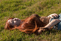 A beautiful redhead sleeping in the meadow Royalty Free Stock Photo