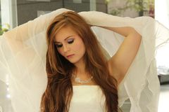Beautiful redhead strikes angelic pose. Beautiful caucasian strikes an angelic pose with an off white strapless dress. She lifts her arms up holding scarf or Royalty Free Stock Photos