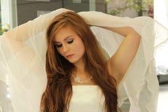 Beautiful redhead strikes angelic pose Royalty Free Stock Photos