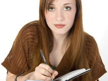 Beautiful Redhead Teen Writing in Datebook. Beautiful young teen girl with red hair and deep green eyes writing in her datebook. Shot in studio over white Royalty Free Stock Photography