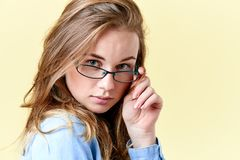 Beautiful redhead teenager girl with freckles wearing reading glasses, smiling teen portrait. On yellow background Stock Images