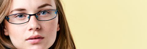 Beautiful redhead teenager girl with freckles wearing reading glasses, smiling teen portrait. On yellow background royalty free stock image
