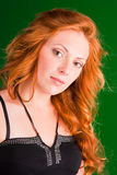 Beautiful redhead woman. Beautiful red-haired woman with a worried look in black sarafan on a green background Royalty Free Stock Images