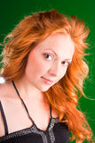 Beautiful redhead woman. Beautiful red-haired woman with a look of interrogative in black sarafan on a green background closeup Stock Image