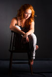 Beautiful redhead woman. Portrait of a beautiful redheaded woman in a chair on a dark background Royalty Free Stock Photos