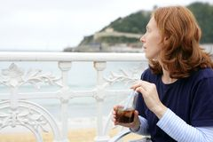Beautiful redhead woman drinking beverage Royalty Free Stock Photography