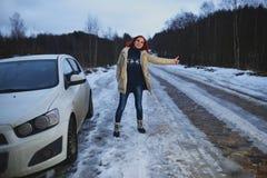 Beautiful redhead woman hitchhiking by broken car Royalty Free Stock Image