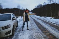 Beautiful redhead woman hitchhiking by broken car Stock Photo