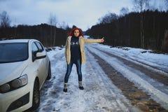 Beautiful redhead woman hitchhiking by broken car Royalty Free Stock Photo