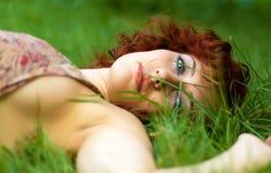 Beautiful redhead woman lying on grass Stock Photo