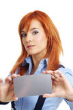 Beautiful redhead woman with notecard. Beautiful redhead businesswoman holding credit card Royalty Free Stock Photos