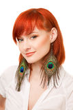 Beautiful redhead woman with peacock earrings Stock Photos