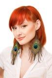 Beautiful redhead woman with peacock earrings. Portrait of young beautiful redhead woman with peacock earrings Stock Photos