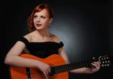 Beautiful redhead woman playing guitar royalty free stock photography