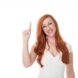Beautiful redhead woman pointing upwards. Beautiful redhead woman pointing above her head with her finger towards blank copyspace, isolated on white Stock Photo