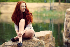Beautiful redhead woman. Portrait af a beautiful redhead woman outdoors. stylish romantic young girl on a walk in the park. red hair and freckles royalty free stock image