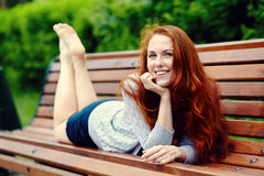 Beautiful redhead woman. Portrait af a beautiful redhead woman outdoors. stylish romantic young girl on a walk in the park. red hair and freckles stock images