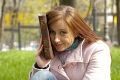 Beautiful redhead woman reading book Stock Photos