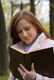 Beautiful redhead woman reading book Royalty Free Stock Image