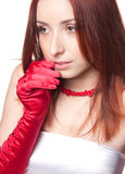 A beautiful redhead woman in red and white close. A closeup portrait of a beautiful redhead woman in red gloves and red necklace Stock Photo