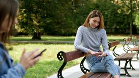 Beautiful redhead woman rest on bench at park, on a blurred foreground girl uses a mobile phone stock video
