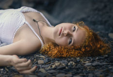 Beautiful redhead woman at the rocky beach. Stock Image