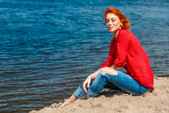 Beautiful redhead woman sitting comfortably and smiling. Looks serene and free and enjoying a sunny day at the beach Stock Photos