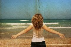 Beautiful redhead woman standing on the beach. Stock Photos