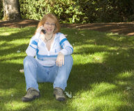 Beautiful Redhead Woman talking on Cell Phone. Sitting on green grass under the shadows of a tree. She's wearing blue jeans and is wearing glasses and a Stock Images