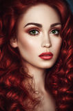 Beautiful redhead woman with wavy hair. Portrait of beautiful redhead woman with wavy hair and green eyes looking at camera royalty free stock photography