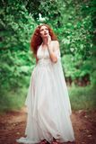 Beautiful redhead woman wearing white dress, in a forest Royalty Free Stock Photo