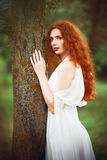 Beautiful redhead woman wearing white dress stands near tree Royalty Free Stock Photos
