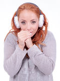 Beautiful redhead woman wearing white earmuffs Royalty Free Stock Photography