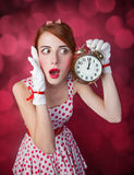Beautiful redhead women with clock. Royalty Free Stock Images