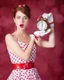 Beautiful redhead women with clock. Royalty Free Stock Image