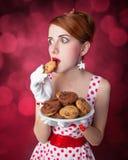 Beautiful redhead women with coockie. Beautiful redhead woman with coockie. Photo in retro style with bokeh at background Royalty Free Stock Photo