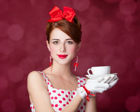 Beautiful redhead women with cup of tea. Beautiful redhead woman with cup of tea. Photo in retro style with bokeh at background Royalty Free Stock Photos