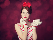 Beautiful redhead women with cup of tea. Beautiful redhead woman with cup of tea. Photo in retro style with bokeh at background Royalty Free Stock Photo