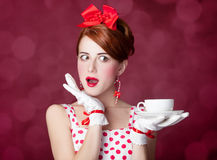 Beautiful redhead women with cup of tea. Beautiful redhead woman with cup of tea. Photo in retro style with bokeh at background Stock Photo