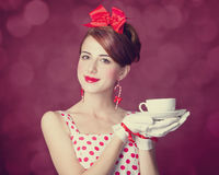 Beautiful redhead women with cup of tea. Beautiful redhead woman with cup of tea. Photo in retro style with bokeh at background Stock Photography