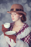 Beautiful redhead women with cup of tea. Royalty Free Stock Photography