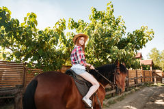 Beautiful redhead young woman cowgirl riding horse in village Royalty Free Stock Images